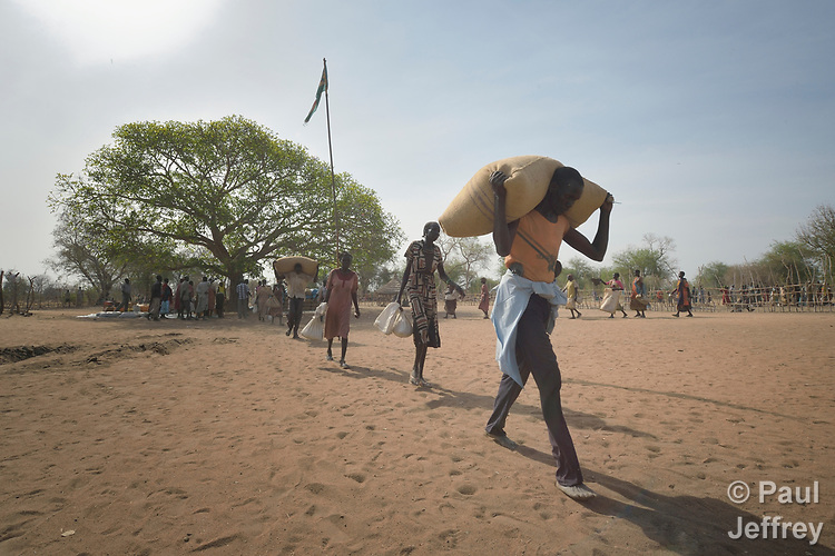 People receive food from the ACT Alliance on April 7, 2017, in Rumading, a village in South Sudan's Lol State where more than 5,000 people, displaced by drought and conflict, remain in limbo. In early 2017, they set out walking for Sudan, seeking better conditions, but were stopped from crossing the border. They remain camped out under the trees at Rumading, eating wild leaves as the rainy season approaches. <br /> <br /> In early April, Norwegian Church Aid, a member of the ACT Alliance, began drilling a well in the informal settlement and distributed sorghum, beans and cooking oil to the most vulnerable families. The man carries a 100 kilogram bag of sorghum that will be divided between several families. <br /> <br /> The ACT Alliance is carrying out the emergency assistance in coordination with government officials and the local Catholic parish.