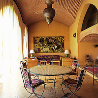 A cast-iron table and chairs and matching wicker armchairs and sofa furnish this informal living area