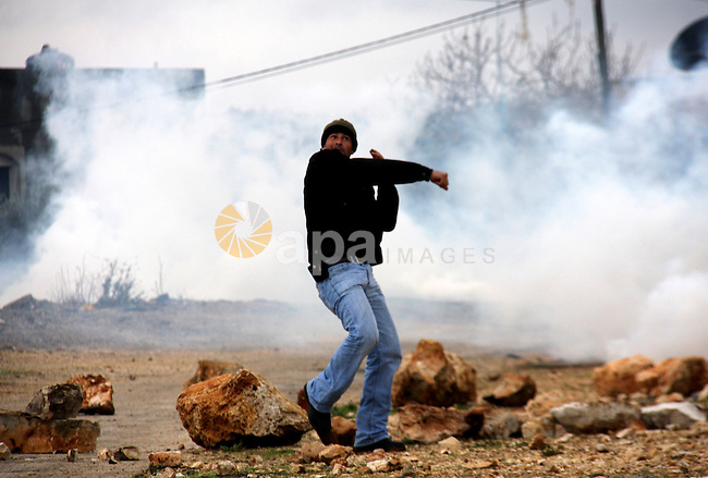 A Palestinian demonstrator throws a stone at at Israeli security forces , who are seeking access to their land near Kufr Qaddum, near the northern West Bank Jewish settlement of Kdumim, Friday, Nov. 18, 2011. Photo by Wagdi Eshtayah