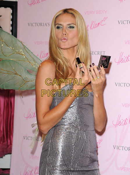 "HEIDI KLUM.At the Victoria's Secret Celebrates The Heidi Collection for ""Very Sexy"" Makeup held at Victoria's Secret at The Grove of LA in Los Angeles, California, USA..October 23rd, 2008   .half length silver strapless dress grey gray lips puckering funny face applying make-up nail varnish polish red                                                                 .CAP/DVS.©Debbie VanStory/Capital Pictures."