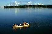 Rio Negro, Brazil. Amazon caboclo family paddling a small canoe; Amazonas State.