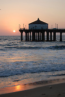 Manhattan Beach, California pier at sunset with water reflection