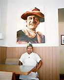 USA, New Mexico, cook sitting under John Wayne painting, Frontier Restaurant, Albuquerque
