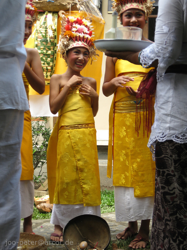 young balinese dancers receiving blessings after   sacred dance pendet for purifying family house compound in larger, day-long ceremonies, North of Ubud,   Bali, archipelago Indonesia, 2010