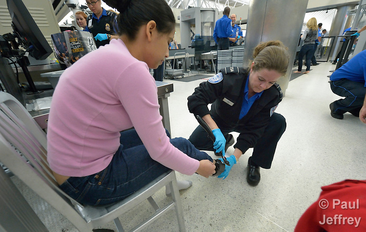Mirna Vasquez, a refugee from El Salvador, has her ankle monitor swabbed by a TSA official in the airport in San Antonio, Texas, on December 2, 2015. Penado fled El Salvador with her daughter to escape gang-related violence. After requesting political asylum in the United States, they were held for several days by immigration officials and then released, although she wears an ankle monitors. They stayed briefly in a shelter run by the Refugee and Immigrant Center for Education and Legal Services (RAICES) and supported by a coalition of San Antonio churches, then flew to another location in the U.S. while they await final decisions on their asylum petition.