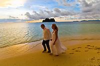 Couple walking on the beach after their sunset wedding ceremony, Vomo Island Resort, Fiji Island