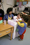 Berkeley CA Two-year-old children cleaning up their lunch dishes at infant day care center