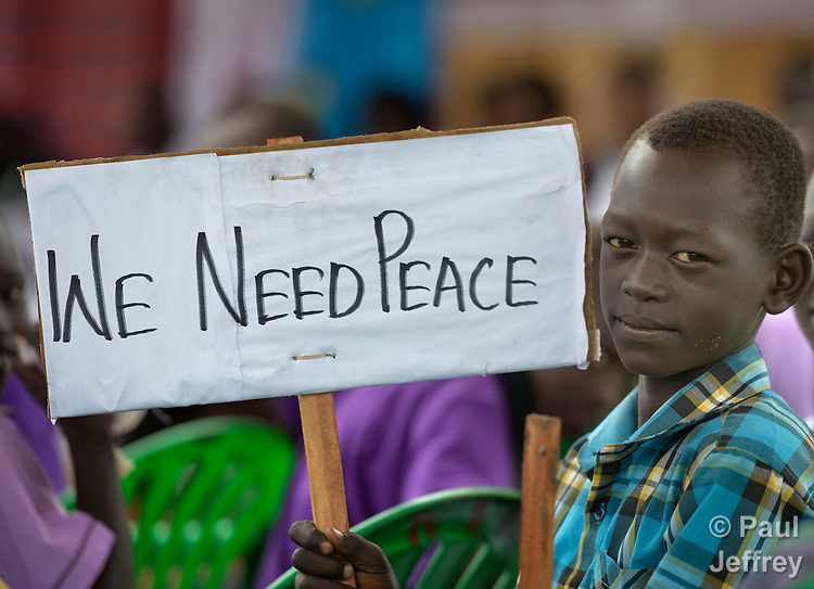 A boy holds a sign at a church-sponsored women's peace rally in Juba, South Sudan.