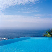 The infinity pool appears to reach out into the Pacific Ocean and the sky