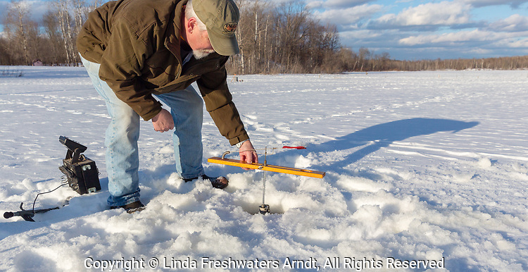Wisconsin fisherman preparing a tip-up for ice fishing.