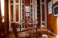 Bowed storage cupboards at one end of the dining room house a collection of English porcelain