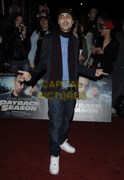 Adam Deacon.The 'Payback Season' UK film premiere, Odeon Covent Garden cinema, Shaftesbury Avenue, London, England..March 6th, 2012.half length black blue suit jacket burgundy maroon scarf hat beanie hands arms jeans denim.CAP/CAN.©Can Nguyen/Capital Pictures.