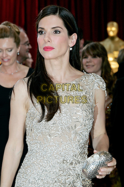 SANDRA BULLOCK.82nd Annual Academy Awards - Oscars.Kodak Theatre, Hollywood, California, USA.7th March 2010.arrivals half length silver gold beige silk satin pink lipstick dress clutch bag .CAP/JE  .©James Eden/Capital Pictures.