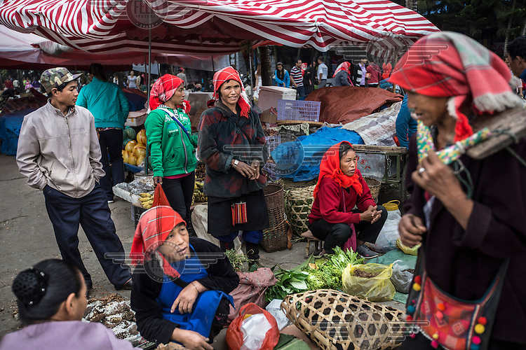 Ethnic Shan women sell vegetables in the market in Mong La. <br /> The town of Mong La on the Burma - China border in western Burma (Myanmar) is technically in Burma but relies on most infrastructure - electricity, telecommunications - on neighbouring China. The main currency used here is the Chinese yuan. The town is in the middle of the so-called &quot;Golden Triangle&quot; and specialises in gambling and the sale of poached and endangered species. Tiger skins, rhino horns, pangolins and other creatures are freely traded here and many are available to eat. Prostitution is rife and just outside the town a bear farm keeps between 500 and 600 bears which are kept in captivity for their bile which is harvested for medicinal use.