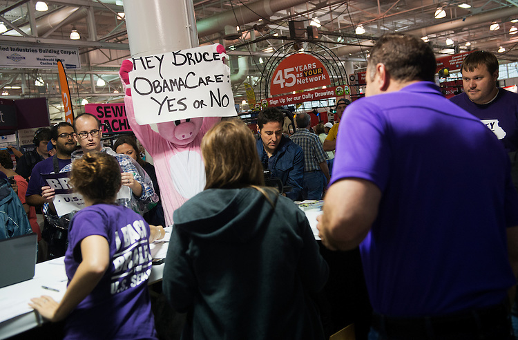 UNITED STATES - AUGUST 07: A heckler holds a sign taunting Senate candidate Rep. Bruce Braley, D-Iowa, about the Affordable Care Act at the 2014 Iowa State Fair in Des Moines, Iowa, August 7, 2014. (Photo By Tom Williams/CQ Roll Call)