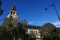 A lateral view of the church of Saint Germain in Paris, with its bell tower, trees and a street lamp, in a sunny spring day. Digitally Improved Photo.