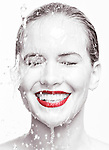 Artistic beauty portrait of a young smiling woman face with red lipstick with water running over it. Isolated on white background. Selective black and white. Image © MaximImages, License at https://www.maximimages.com