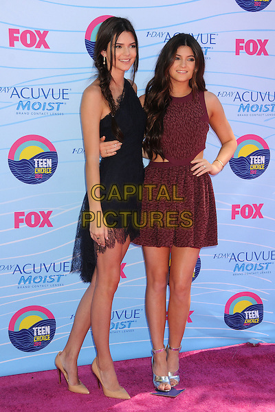 Kendall Jenner and Kylie Jenner.FOX's 2012 Teen Choice Awards held at The Gibson Ampitheatre in Universal City, California, USA..July 22nd, 2012.full length red black one shoulder cut out away sides lace blue sisters siblings family sleeveless dress hand on hip.CAP/ADM/BP.©Byron Purvis/AdMedia/Capital Pictures.