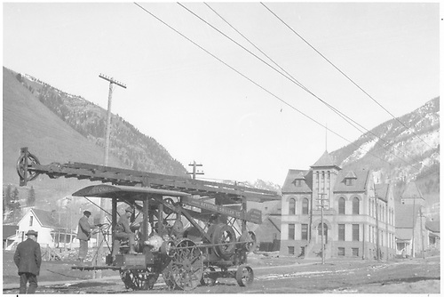 Side view of an early Keystone Drilling Co. drilling rig moving up Matz Ave. with the Dolores County courthouse in the background.<br /> Rico, CO