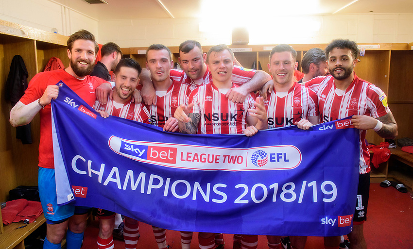 Lincoln City players, from left, Josh Vickers, Tom Pett, Harry Toffolo, Matt Rhead, Harry Anderson, Shay McCartan and Bruno Andrade celebrate in the changing room after winning the league<br /> <br /> Photographer Chris Vaughan/CameraSport<br /> <br /> The EFL Sky Bet League Two - Lincoln City v Tranmere Rovers - Monday 22nd April 2019 - Sincil Bank - Lincoln<br /> <br /> World Copyright © 2019 CameraSport. All rights reserved. 43 Linden Ave. Countesthorpe. Leicester. England. LE8 5PG - Tel: +44 (0) 116 277 4147 - admin@camerasport.com - www.camerasport.com