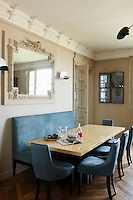 The table in the kitchen/dining area is made from layers of toughened leather and the banquette and dining chairs covered in blue Oregan leather, a colour echoed in the four photographic prints by Guido Mocafico