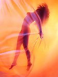 Abstract artistic photo of a beautiful nude woman graceful silhouette floating suspended behind sheer surreal glowing veil in vivid red and yellow colors