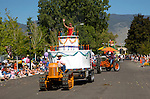 A woman waves from the top of a cake parade float pulled by an Oliver tracklayer tractor during Carson Valley Days Parade celebrating the 125th birthday of Gardnerville/Minden.