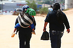 HUSBAND and WIFE WALK to MARKET WITH TODDLER in SLING OVER WIFE's SHOULDER. <br /> (2)