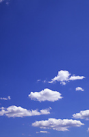Blue sky with scattered cumulus clouds at the bottom of the frame.