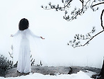 Woman in white dress standing on a cliff meditating with spread hands embracing the world and the nature. Spiritual concept. Wintertime outdoor scenery.