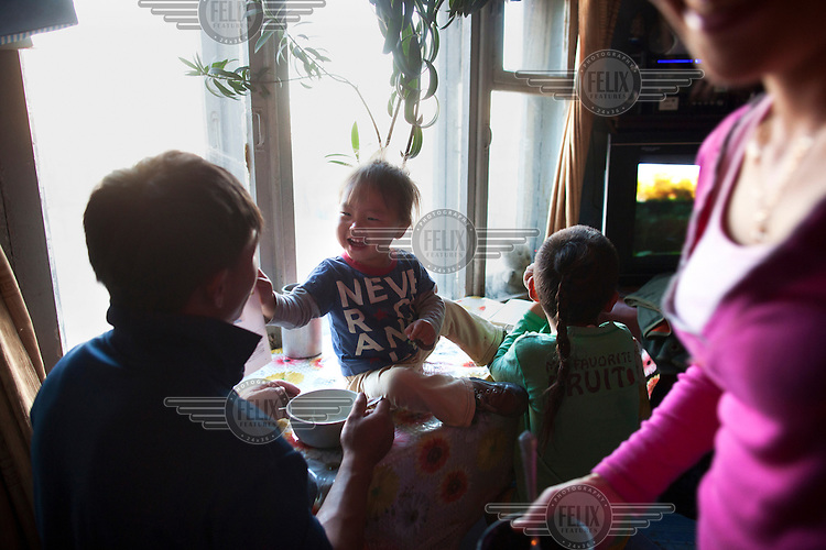 Children having lunch with their mothers inn the family home.in the home.