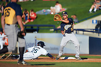 Burlington Bees first baseman Matt Thaiss (12) waits for a throw as Rashad Brown (25) dives back to the bag during a game against the West Michigan Whitecaps on July 25, 2016 at Fifth Third Ballpark in Grand Rapids, Michigan.  West Michigan defeated Burlington 4-3.  (Mike Janes/Four Seam Images)
