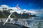 Alaska Marine Highway System sailing through Lynn Canal, Inside Passage, SE Alaska on a sunny day.  Snow capped mountains are towering over the ocean. American flag in the scene.