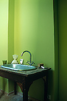 A washstand fashioned out of an old table supports an oval metal wash basin in this bright green bathroom
