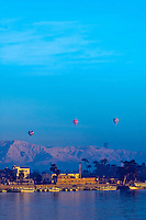 Hot air balloons floating toward the Valley of the Kings, seen from the Nile River in Luxor, Egypt