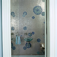 In the powder room metallic mosaic tiles are matched by a full length mirror and a glass hand basin