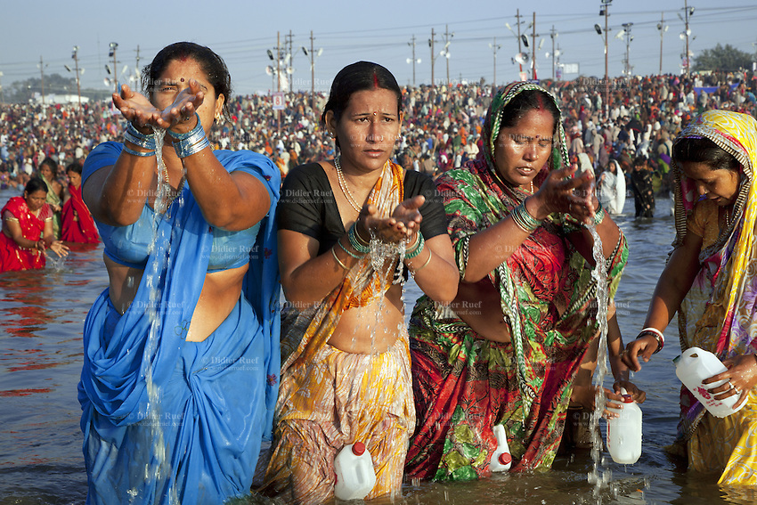 India. Uttar Pradesh state. Allahabad. Maha Kumbh Mela. Indian Hindu devotees take a holy dip at Sangam. Three women offer water to Mother Ganges because the river is considered a deity. The four women have a plastic container to collect Ganges water which will bebrought back home. The Kumbh Mela, believed to be the largest religious gathering is held every 12 years on the banks of the 'Sangam'- the confluence of the holy rivers Ganga, Yamuna and the mythical Saraswati. In 2013, it is estimated that nearly 80 million devotees took a bath in the water of the holy river Ganges. The belief is that bathing and taking a holy dip will wash and free one from all the past sins, get salvation and paves the way for Moksha (meaning liberation from the cycle of Life, Death and Rebirth). Bathing in the holy waters of Ganga is believed to be most auspicious at the time of Kumbh Mela, because the water is charged with positive healing effects and enhanced with electromagnetic radiations of the Sun, Moon and Jupiter. The Maha (great) Kumbh Mela, which comes after 12 Purna Kumbh Mela, or 144 years, is always held at Allahabad. Uttar Pradesh (abbreviated U.P.) is a state located in northern India. 8.02.13 © 2013 Didier Ruef