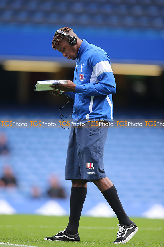 Wilfried Zaha of Crystal Palace checks his phone whilst reading the match day programme during Chelsea vs Crystal Palace, Premier League Football at Stamford Bridge on 1st April 2017