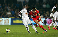 SWANSEA, WALES - MARCH 16: Marvin Emnes of Swansea (L) is challenged by Steven Gerrard of Liverpool (R) during the Premier League match between Swansea City and Liverpool at the Liberty Stadium on March 16, 2015 in Swansea, Wales