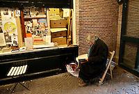Nederland Amsterdam  2017. Universiteit van Amsterdam ( UvA ).  Boekenmarkt bij de Oudemanhuispoort.  Verkoper bekijkt een boek.  Foto Berlinda van Dam / Hollandse Hoogte