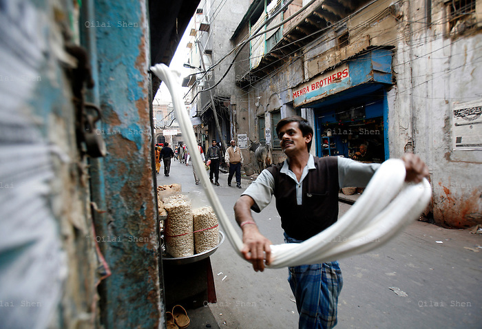 A man twists and turns a wad of syrup used to make sweets in Old Delhi, India on Wednesday, 17 January 2007.