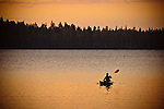 Woman kayaking at sunset on Gold Lake, Sierra County, Northern California.