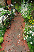 Bicycle on brick path in garden, bench, flowers, ferns, gate, wall