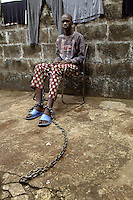 "Alpha  (15) has two chains on his feet, one of them chained to a chair he carries with him for 24 hours a day...City Of Rest is, according to a sign over the entrance, a ""counselling & mini-rehabilitation centre for drug addicts, alcoholics, traumatised and delinquent youths"". It is the only place in Sierra Leone to offer any rehabilitation for these people. Though the methods used may be seen as unusual by western standards, the pastor in charge claims increasing success. The treatment consist of chaining the youths to chairs, prayers, plenty of food and rest. © Fredrik Naumann Freetown, Sierra Leone."