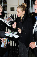 """SIENNA MILLER .Departed after the first preview performance of """"Flare Path"""", Haymarket, London, England, UK, 4th March 2011..half length hair up bun signing autographs fans black coat .CAP/CAN.©Can Nguyen/Capital Pictures."""