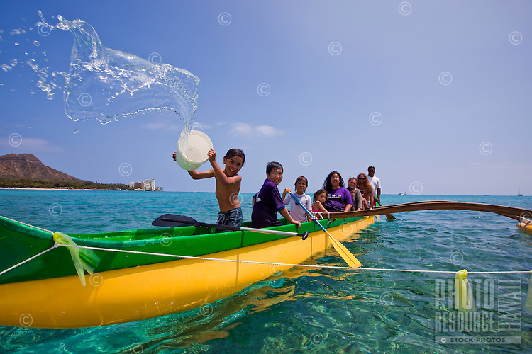Local boy bailing a Hawaiian outrigger canoe ride off the shores of Waikiki