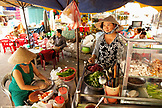 VIETNAM, Saigon, Ho Chi Minh City, Street kitchen owned by 'the Lunch Lady' near 23 Hoang Sa, in District 1, the Lunch Lady serves food while another woman rolls goi cuon (fresh summer rolls)