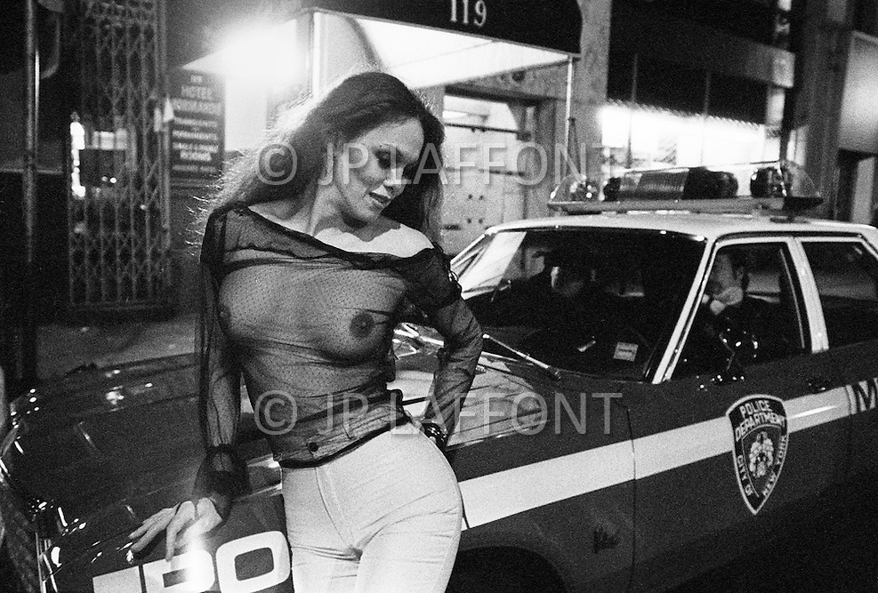 May, 1980. Manhattan, New York City, NY. A prostitute leans playfully on a cop car on 42nd Street Times Square. The police struggled to keep up with onslaught of crime in the area and at times seemed to be playing a friendly game of cat and mouse with the hookers. <br /> <br /> Manhattan, New York City, NY, Mai, 1980. 1 heure du matin : Cette prostituée nargue les policiers en prenant des poses aguichantes contre leur voiture. Les policiers sont bons enfants et acceptent en riant ces situations extrêmes.