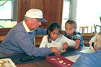 Grandpa age 60 and granddaughters playing scrabble game age 7 & 8.  Cedarville  Michigan USA
