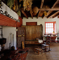 Traditional kitchen utensils are displayed around an original fireplace with dried herbs and flowers hanging from the ceiling
